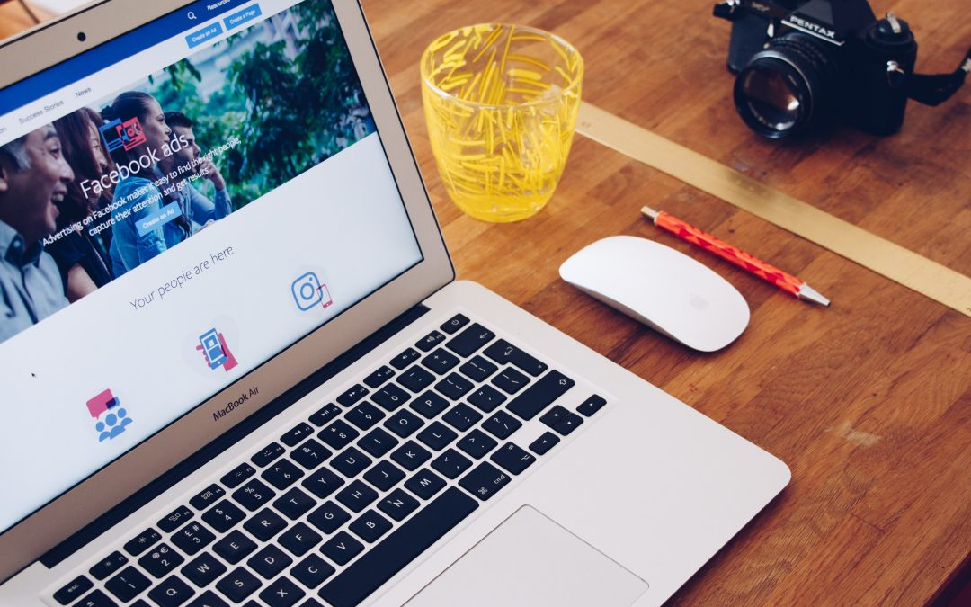 Laptop, cup, mouse, pen, and camera on a wooden table. The laptop screen is showing the Facebook Ads homepage. Photo by Will Francis on Unsplash. @willfrances