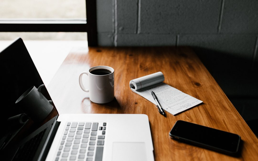 A dark wood desk with a laptop, notebook and pen, white mug, and black mobile phone. Photo by Andrew Neel on Unsplash.